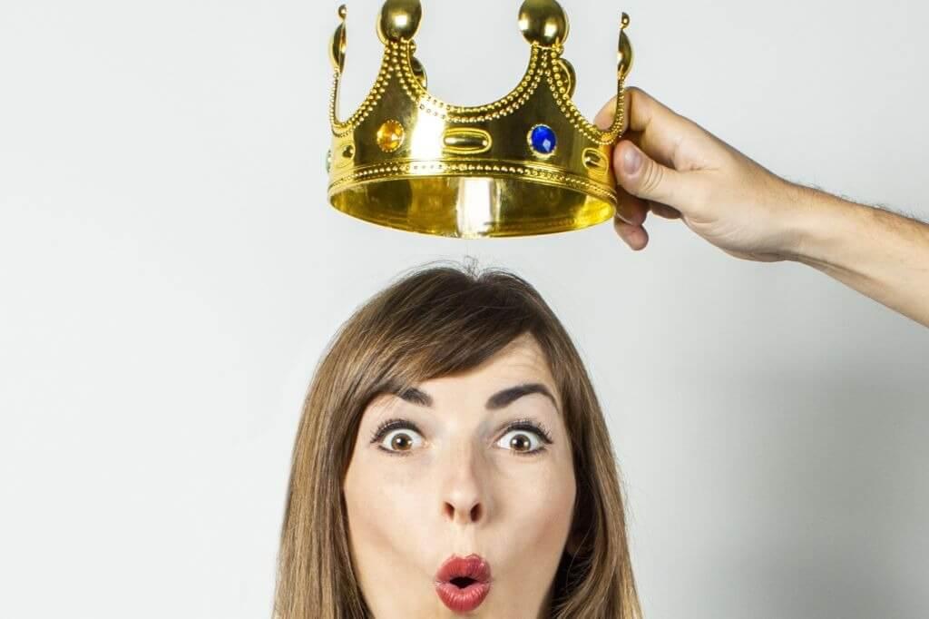 mulher maquiada usa coroa como fantasia de carnaval
