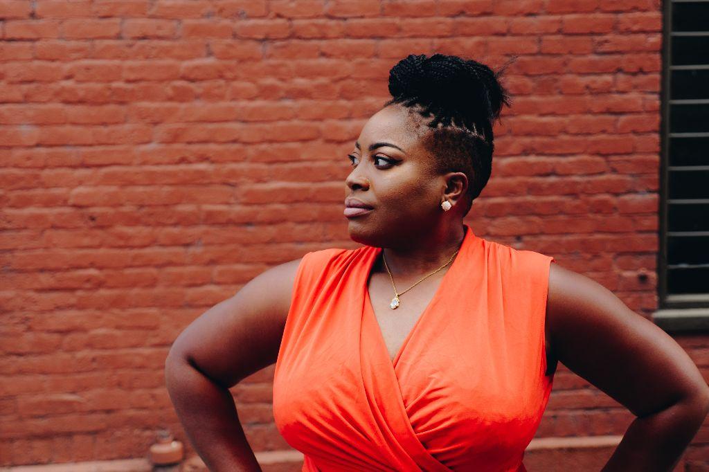 Mulher usa blusa laranja e olha para o lado